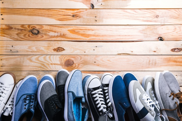 Various pairs of  sneakers laid on the wooden floor