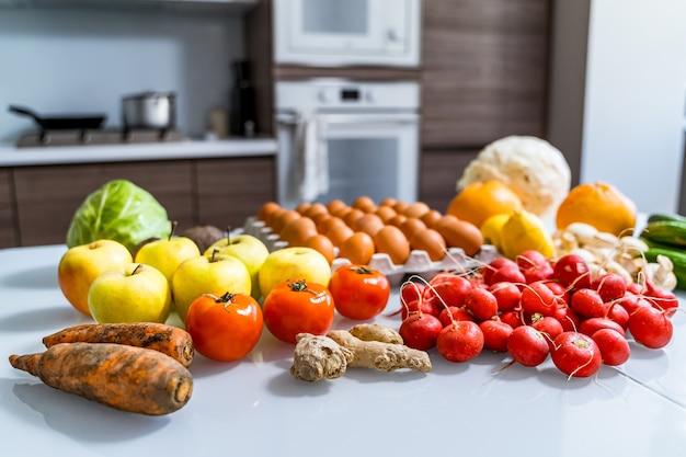 Различные продукты палеодиеты на белом столе. вид сверху. здоровая диета. свежие вкусные овощи, фрукты и яйца фермеров.