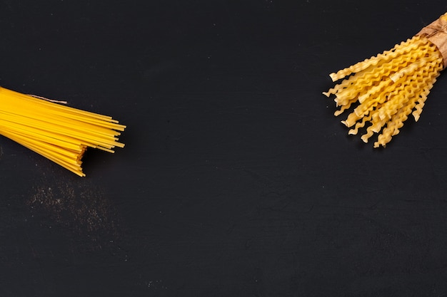Various pasta on black surface
