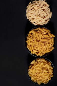 Various pasta. cooking concept. top view on dark beton background wuth copy space