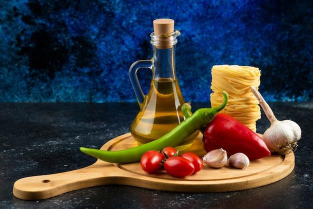 Vari pasta, olio e verdure su tavola di legno.