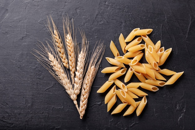 Various pasta and wheat on a black stone background. top view with copy space.
