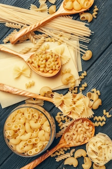 Various pasta on wooden spoons and bowls