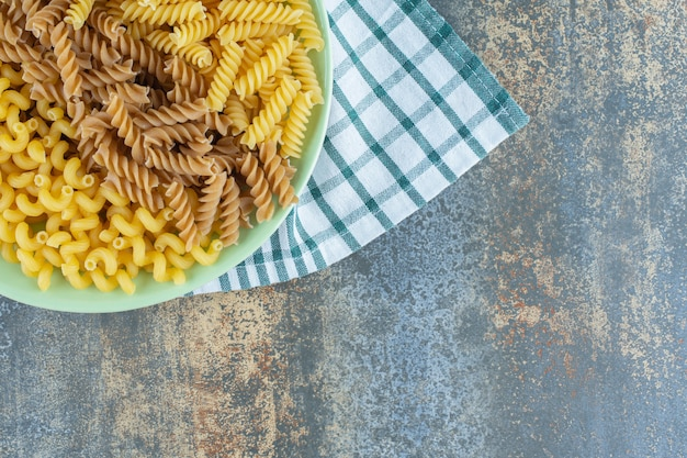 Различные макаронные изделия в миске на полотенце, на мраморной поверхности.
