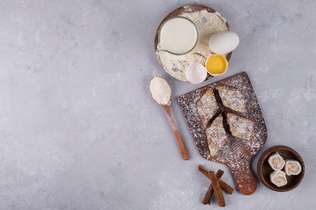 Vari dolci e ingredienti sul piatto di legno