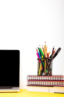 Various pens and pencils in holder over stacked notebook near laptop