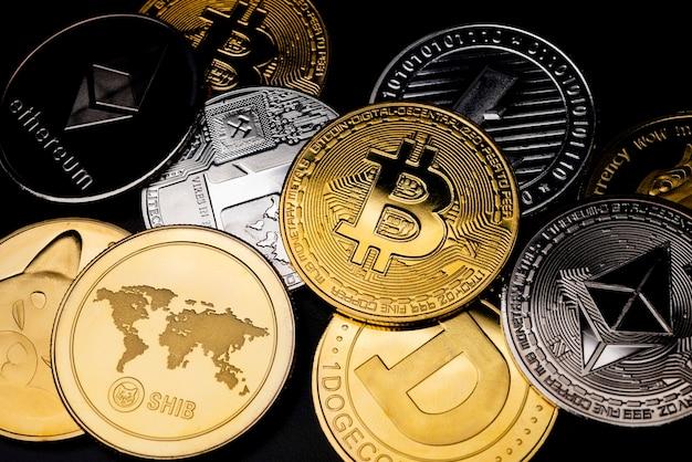검정 배경 위에 흩어져 있는 다양한 실제 금속 동전. 암호 화폐 개념.