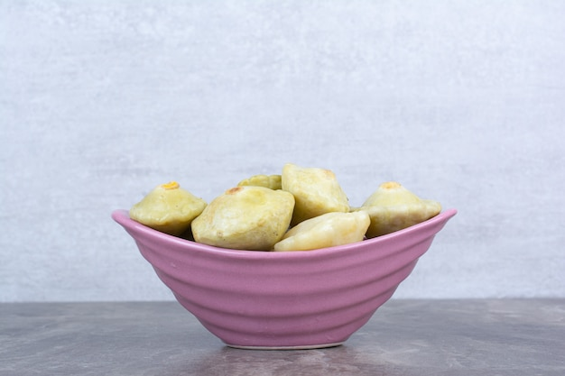 Various pickled fruits in pink bowl.