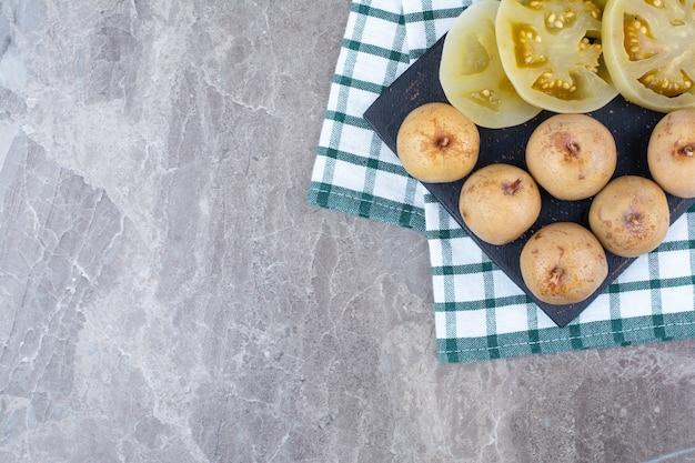 Различные маринованные овощи и фрукты на темной доске. Бесплатные Фотографии