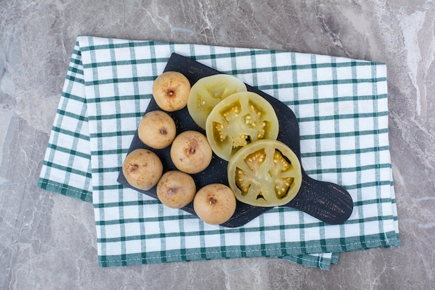 Различные маринованные овощи и фрукты на темной доске.
