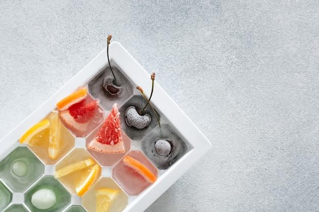 얼음에 얼린 다양한 과일과 열매가 밝은 돌 배경의 쟁반에 놓여 있습니다