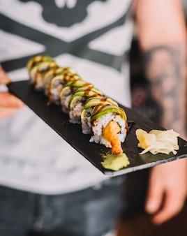 Различные кусочки суши на черном столе