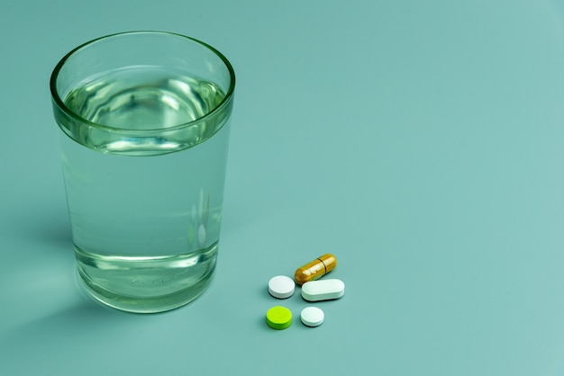 Various pills and glass of water on gray background