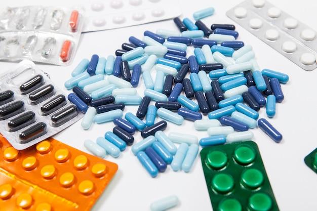 Различные таблетки в блистерах и капсулах на белом фоне