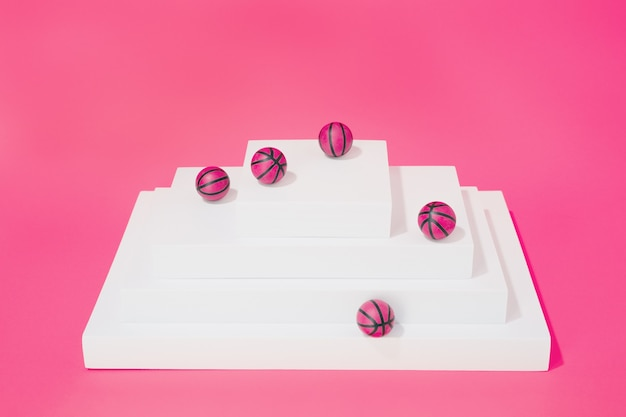 Various pink basketballs on various structures on pink background. sport and competition.copy space. 3d illustration