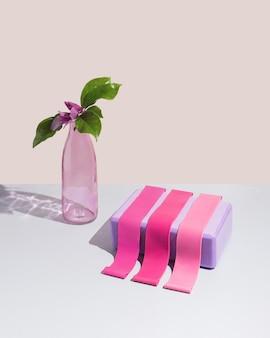 パステルベージュの背景にさまざまなピンクのフィットネス弾性バンドと紫のヨガブロック。ガラス瓶と美しいマグノリアの花。春や夏の家やジムのトレーニングシーン。