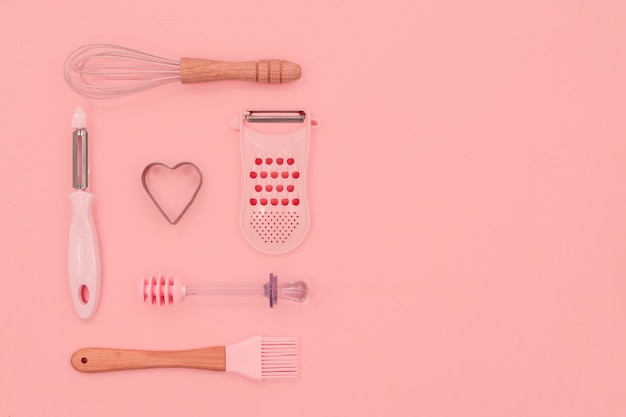 Various pink kitchen utensils on abstract pink background. greater, whisk and iron cooking form. top horizontal view copyspace love cookong concept