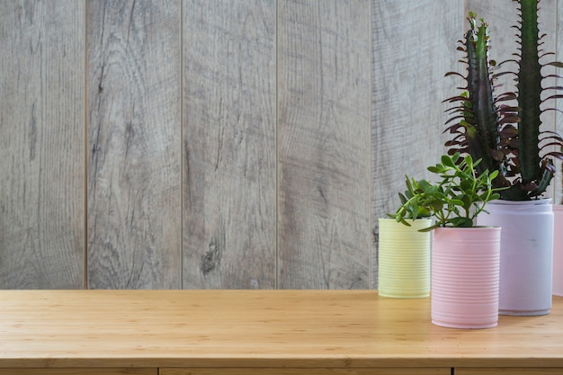 Various plant in the painted recycle cans on wooden table