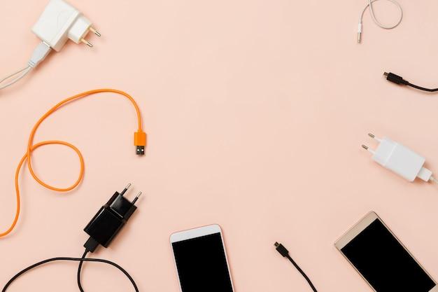 Различные вилки и кабели и смартфоны на пастельном столе