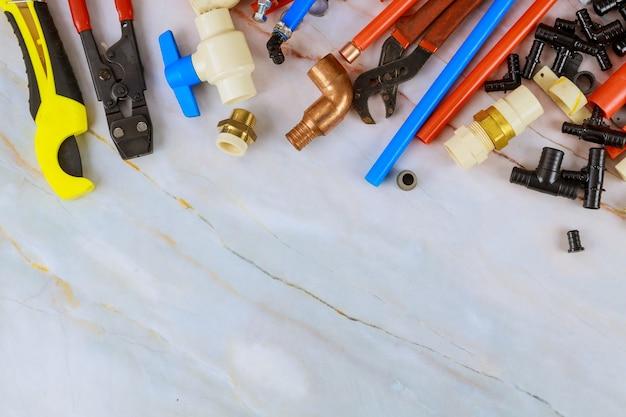 Различные инструменты сантехников, фитинги для сантехнических материалов, включая медную трубу, угловое соединение, гаечный ключ и гаечный ключ.