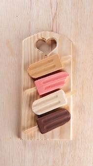 다양한 아이스 캔디가 나무 판자 배경에 놓여 있습니다. 카라멜, 딸기, 바닐라, 초콜릿 맛. 평면도. 복사