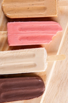 На фоне деревянной доски размещены различные фруктовые мороженое. вкус карамели, клубники, ванили и шоколада. вид сверху