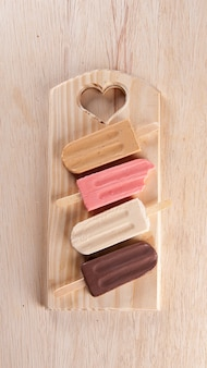Various popsicles are placed on the wooden board background. caramel, strawberry, vanilla and chocolate flavor. top view. copy sapce