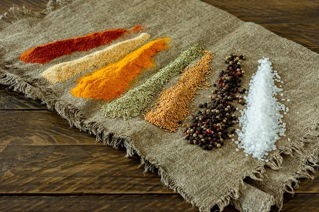 나무 테이블에 다양한 가루 향신료. 텍스트, 음식 또는 요리 개념을 위한 공간이 있는 배경.