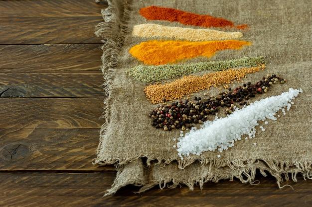 나무 테이블에 다양한 분말 향신료. 텍스트, 음식 또는 요리 개념을 위한 공간이 있는 배경.