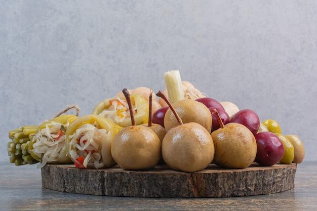 Различные консервированные овощи на доске.