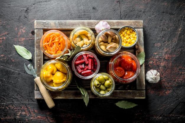 Различные консервированные овощи на деревянном подносе. на темной деревенской поверхности