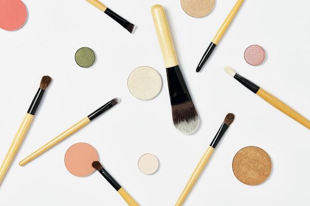Различные профессиональные кисти для макияжа с деревянной коричневой ручкой случайным образом лежат на белом фоне вокруг множества разноцветных круглых палитр теней для макияжа. вид сверху, плоский.