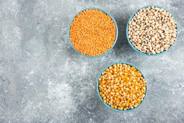 大理石のテーブルに、さまざまな生の豆、とうもろこし、赤レンズ豆。