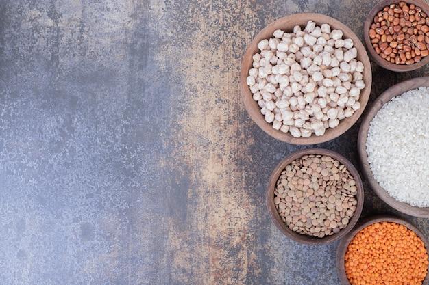 나무 그릇에 다양한 생 콩, 렌즈 콩 및 쌀.
