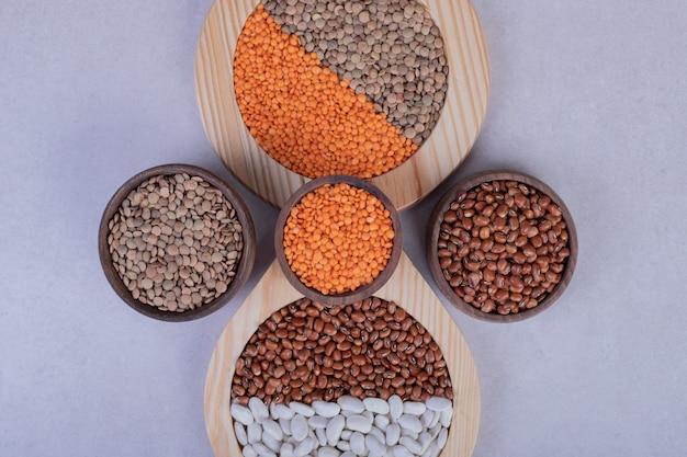 Vari fagioli crudi e lenticchie in ciotole di legno.