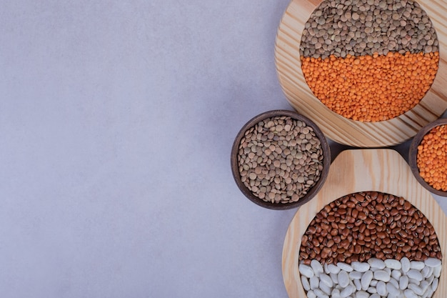 Various raw beans and lentils in wooden bowls.