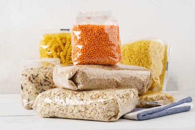 다양한 원시 가루, 시리얼 곡물 및 파스타를 식탁에 투명 비닐 봉지에 담았습니다. 요리 재료.