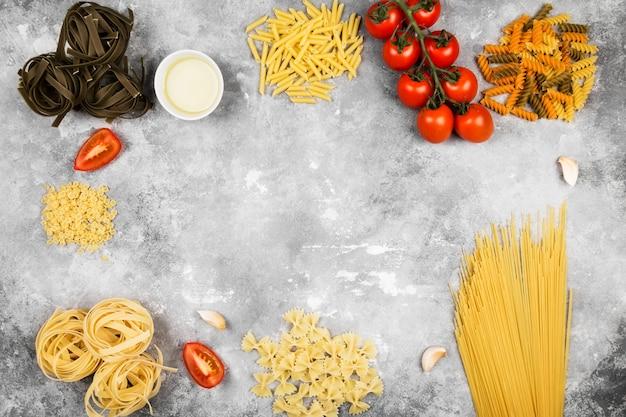 Различные сырые макароны и ингредиенты для приготовления пищи (помидоры, оливковое масло, чеснок) на сером фоне. вид сверху, скопируйте пространство. пищевой фон