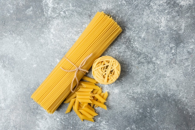 Various raw pasta on marble background. spaghetti, penne, tagliatelle.