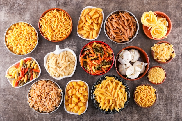 Various raw pasta types plates top view