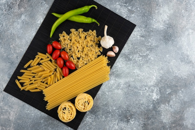 Various raw pasta and vegetables on black bamboo sheet.
