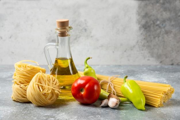 大理石のテーブルにオリーブオイルと野菜のボトルが入った様々な生パスタ。