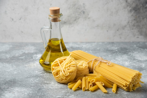 Various raw pasta with bottle of olive oil on marble table.