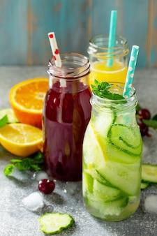 さまざまな軽食は、石のテーブルにデトックスキュウリ水チェリージュースとオレンジジュースを飲みます
