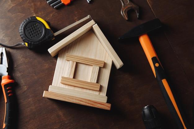 Различные инструменты для ремонта и модели дома. набор инструментов для ремонта на деревянном столе