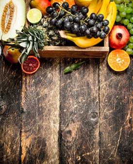 木箱に入った様々な熟した果実。木製のテーブルの上。