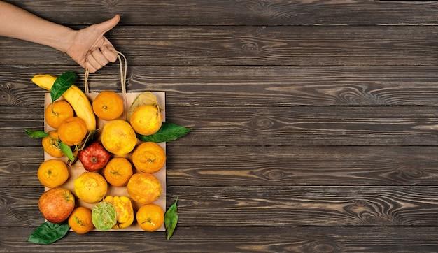 Различные спелые, сырые фрукты в упаковке. женская рука держит пакет, восстановленный темный деревянный стол. вид сверху. идея пищевых бумажных пакетов без отходов. концепция доставки, покупки или пожертвования еды.