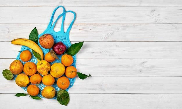 Различные спелые сырые фрукты на тряпичной сети для продуктов на светлом деревянном столе. вид сверху. идея экологически чистых пищевых пакетов с нулевыми отходами. концепция доставки, покупки или пожертвования еды. макет с копией пространства.