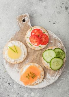 木製にサーモンとチーズ、トマトとキュウリを添えたさまざまな丸い健康的なクラッカー