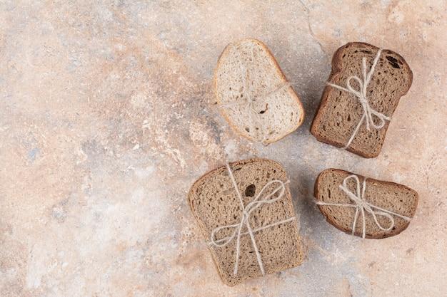 Varie pile di pane di segale su sfondo di marmo